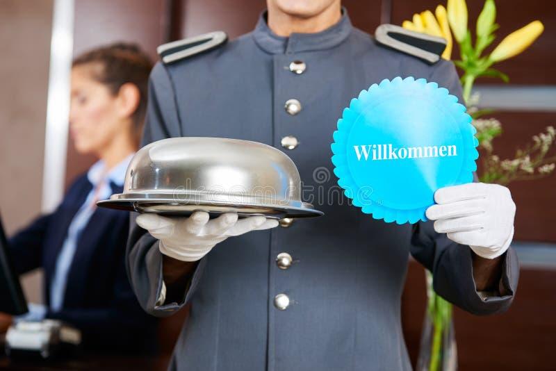 Страница гостиницы держа немецкий знак говоря Willkommen стоковые изображения