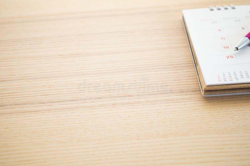 Страница календаря с пунктом ручки на 25th дате на деревянной предпосылке таблицы стоковое изображение rf