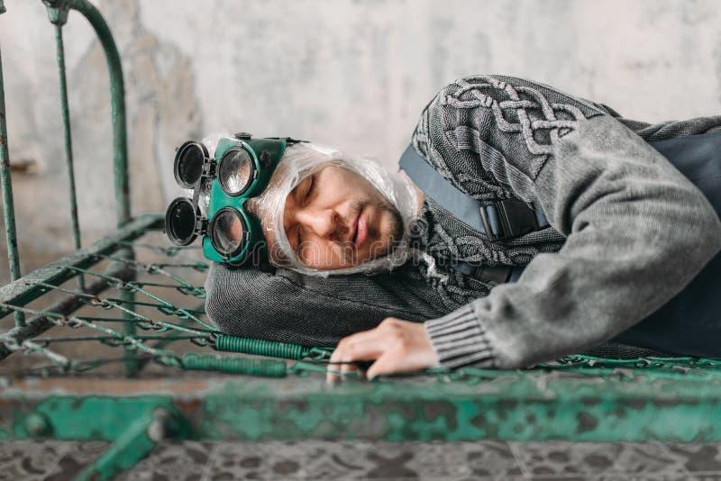 Странный человек оборачивает его голову в фильме и лежит в кровати стоковые изображения rf