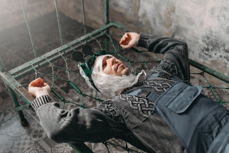 Странный человек оборачивает его голову в фильме и лежит в кровати стоковая фотография