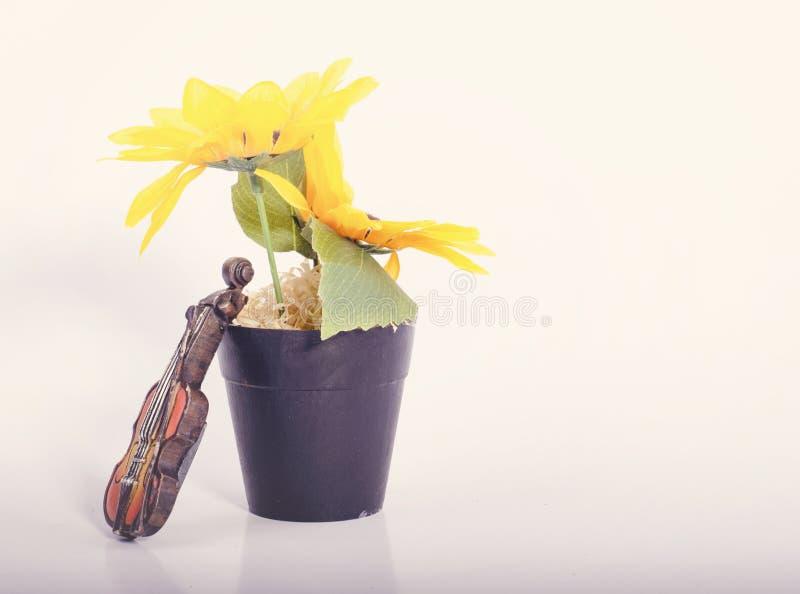 Страсть музыки и концепция хобби, миниатюра скрипки с заводом искусственного цветка на таблице белизны отражения стоковое фото