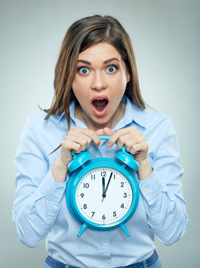 Страх на стороне бизнес-леди держа будильник стоковая фотография