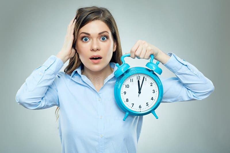 Страх на стороне бизнес-леди держа будильник стоковые изображения