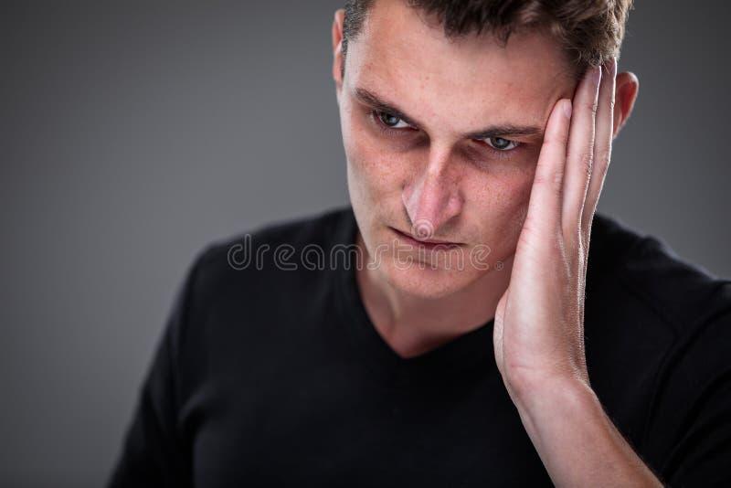 Страх/тревожность/сожаление/неопределенность в молодом человеке стоковая фотография