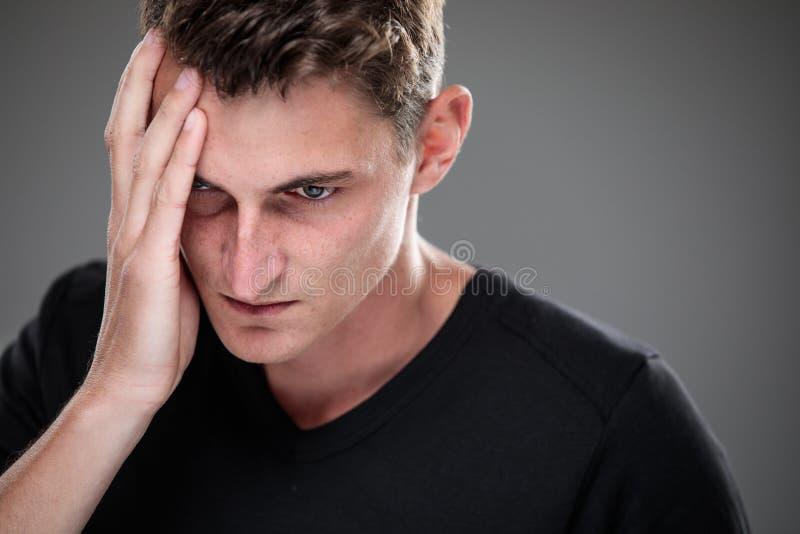 Страх/тревожность/сожаление/неопределенность в молодом человеке стоковая фотография rf