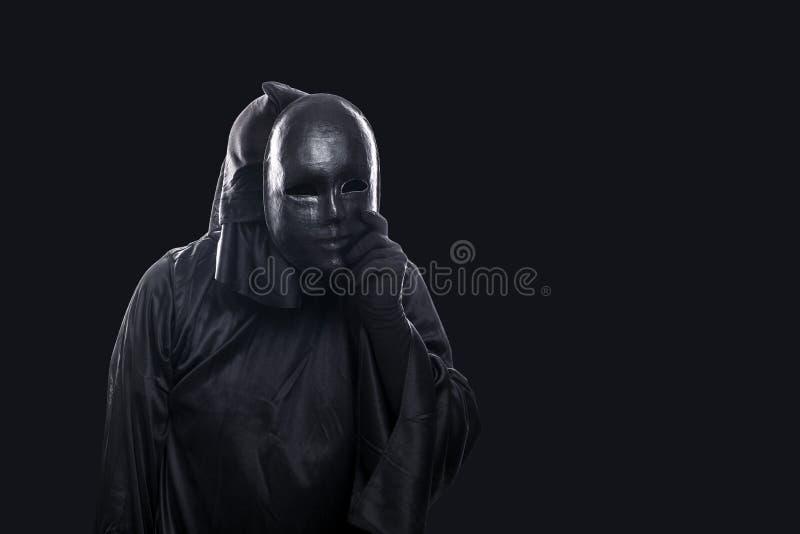 Страшная диаграмма в с капюшоном плаще с маской в руке стоковые фото
