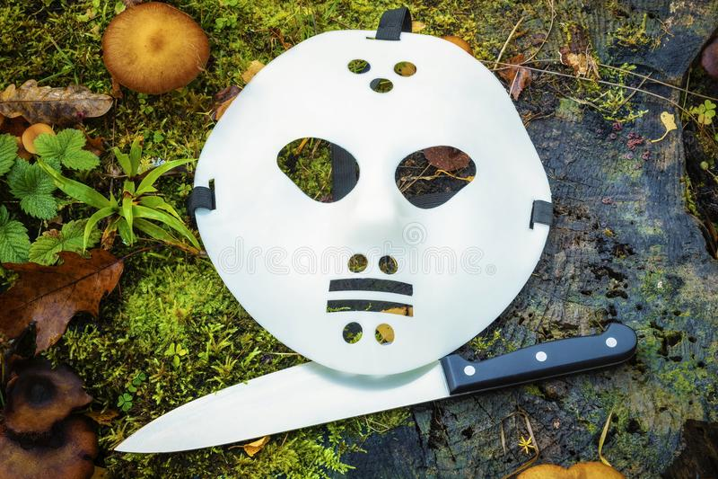 Страшная маска и нож хеллоуина на пне стоковое фото rf
