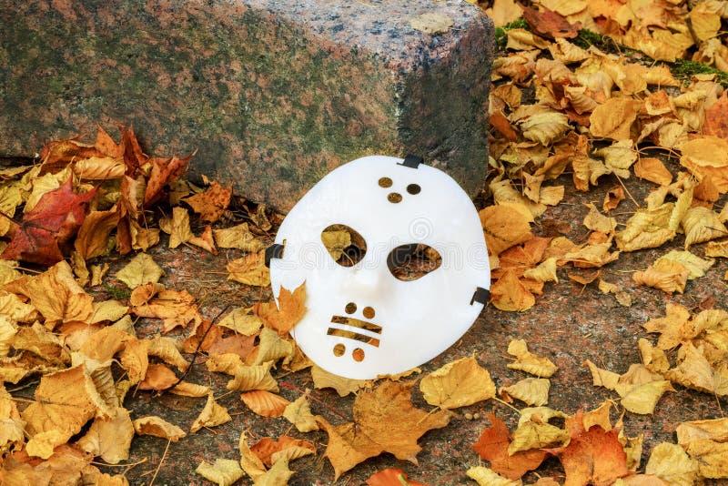 Страшная маска хеллоуина между листьями осени стоковые фото