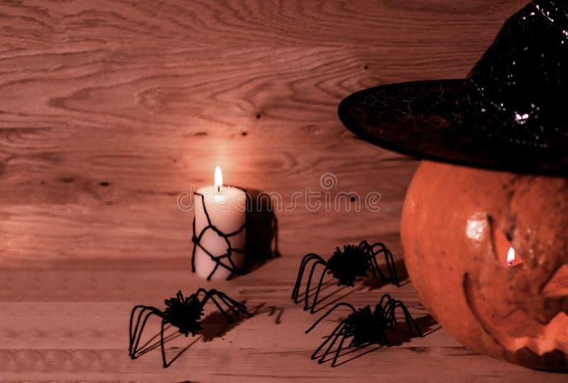 Страшная тыква на хеллоуин в шляпе ведьмы на деревянной предпосылке стоковая фотография rf