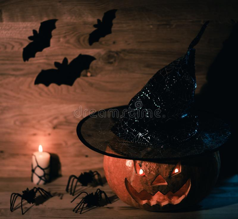 Страшная тыква на хеллоуин в шляпе ведьмы на деревянной предпосылке стоковые изображения