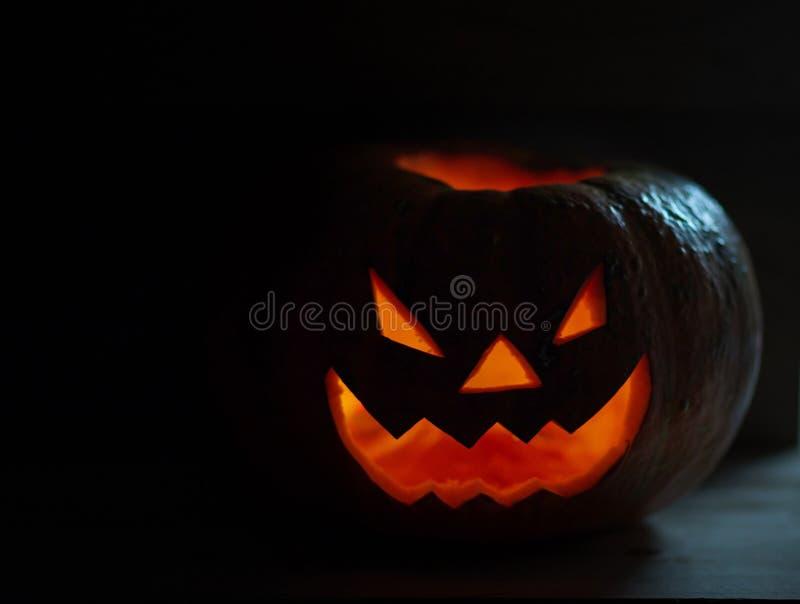Страшная усмехаясь тыква на хеллоуин на черной предпосылке стоковые фотографии rf