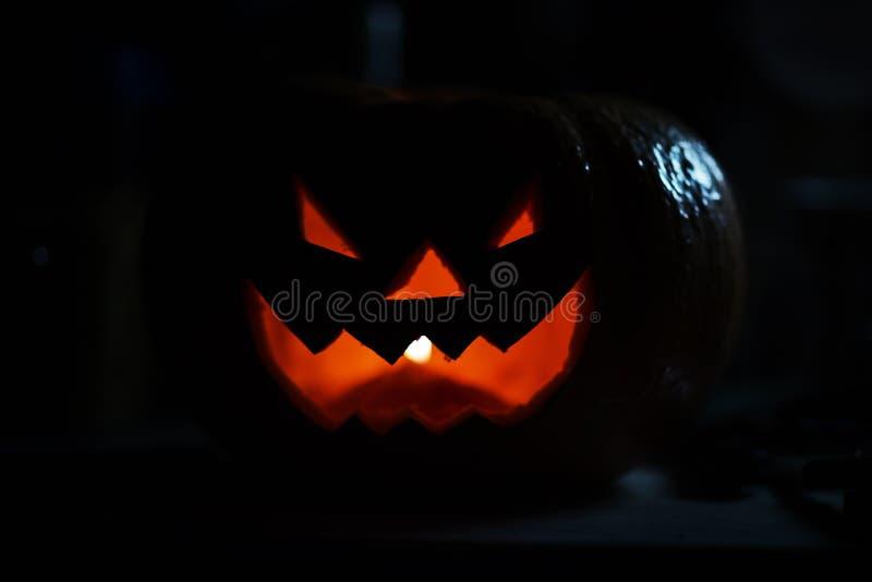 Страшная усмехаясь тыква на хеллоуин на черной предпосылке стоковое изображение