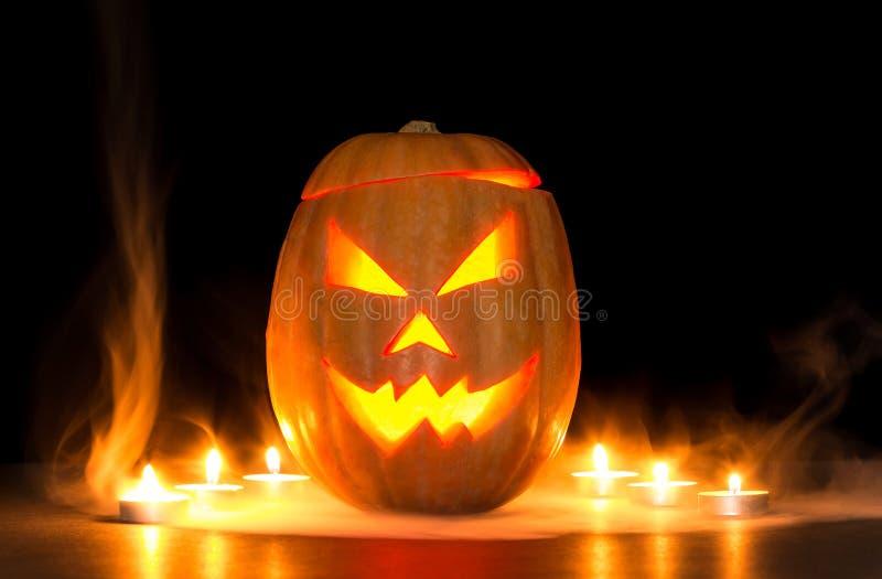 Страшные Джек-o-фонарики тыквы хеллоуина на черноте осветили с малыми круглыми свечами стоковое фото