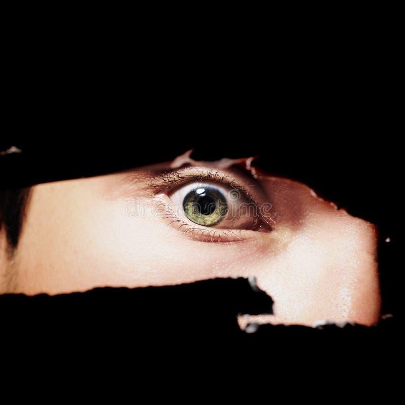 Страшный глаз человека шпионя через отверстие стоковое изображение rf