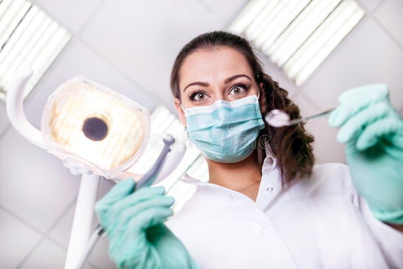 Страшный и смешной дантист работая с пациентом в защитном wor стоковая фотография rf
