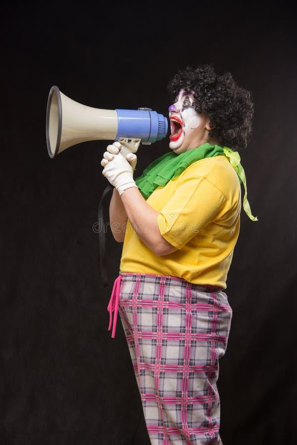 Страшный клоун крича в мегафон на черной предпосылке стоковая фотография rf