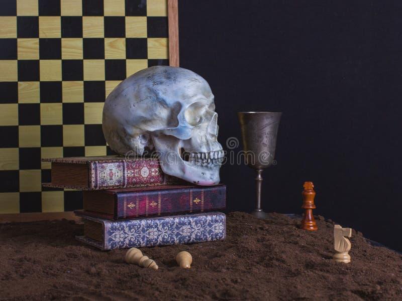 Страшный натюрморт с черепом, шахмат, книгами и кубком вина дальше стоковое фото rf