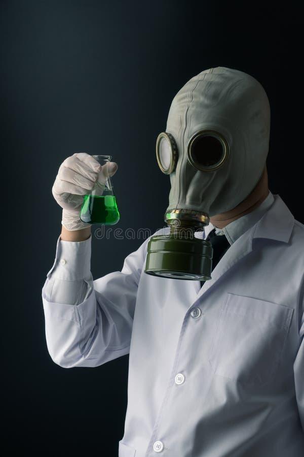 Страшный ученый в маске противогаза держа зеленую токсическую склянку химического вещества стоковое фото