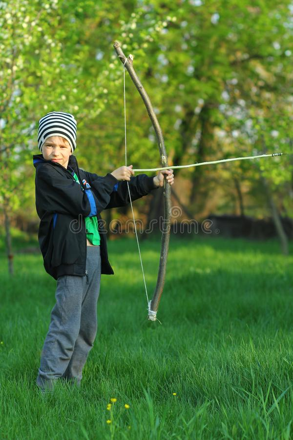 Стрельба мальчика с ручной работы луком и стрелы стоковые фото