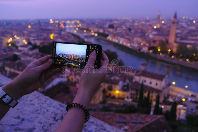 Стрельба с камерой телефона, городом ночи стоковое фото