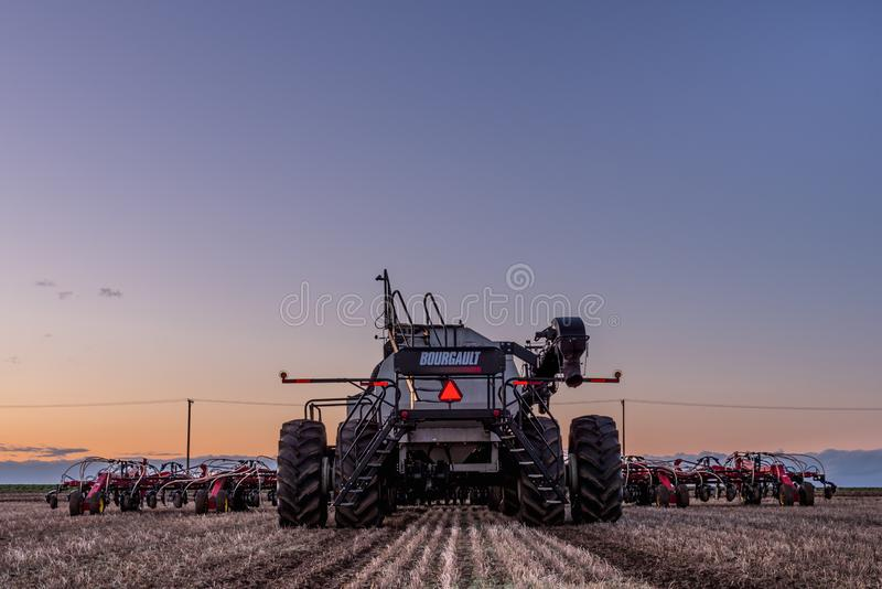 Стремительное течение, SK/Canada- 10-ое мая 2019: Пневматический сверлильный аппарат трактора и Bourgault осеменяя оборудование в стоковое изображение