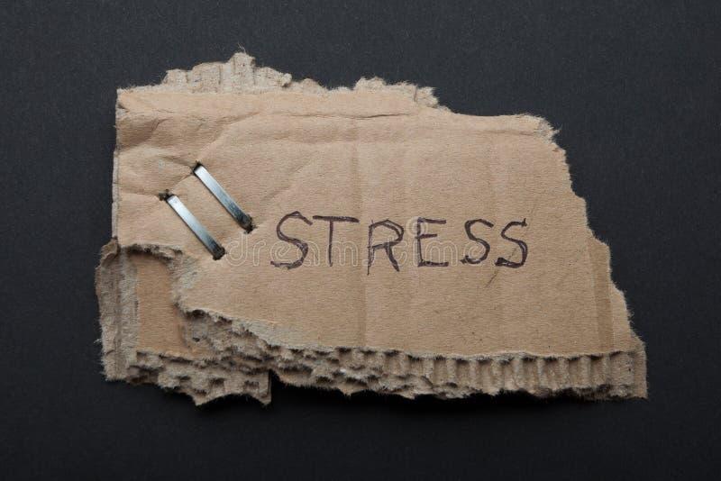 """Стрессы слова """"на сорванной части картонной коробки на черной предпосылке стоковые фото"""