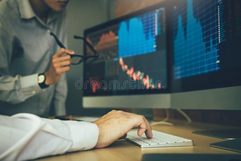 Стресс 2 биржевых маклеров дела и смотреть мониторы показывая финансовую информацию стоковые изображения rf