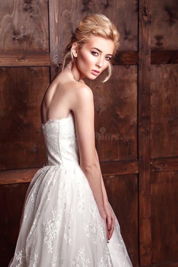 Стрельба красоты моды bridal Красивая невеста моды в платье свадьбы представляя перед древообразной предпосылкой стоковая фотография rf