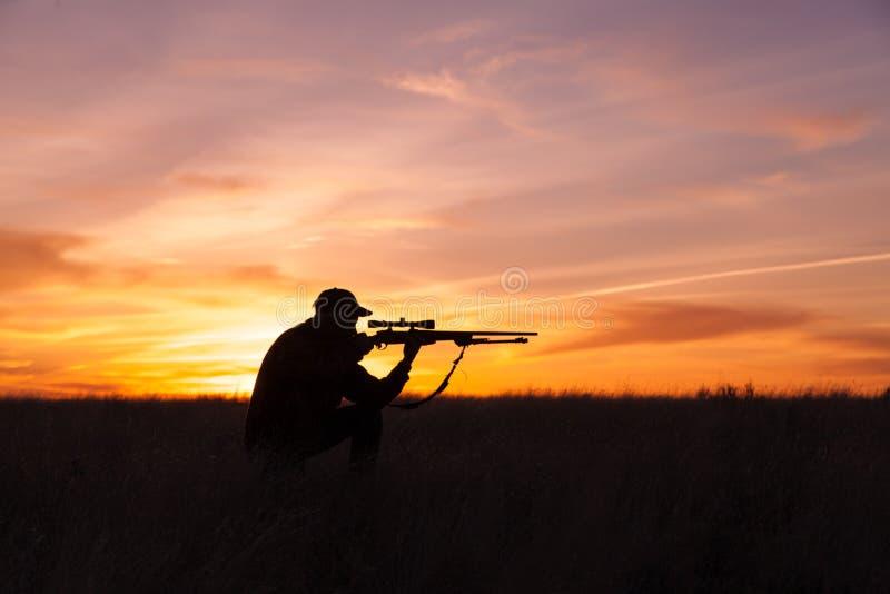Стрельба охотника винтовки вставать в заходе солнца стоковая фотография