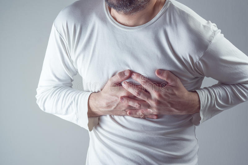 Строгая сердечная боль, человек страдая от боли в груди, имеющ тягостное стоковое фото