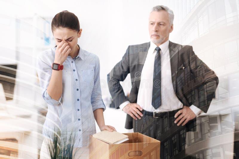 Строгий босс увольняя молодую унылую женщину стоковое изображение rf