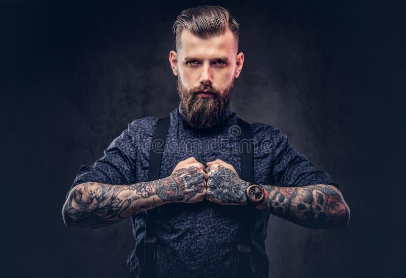 Строгий старомодный парень битника в голубой рубашке и подтяжках, представляя в студии стоковое изображение rf
