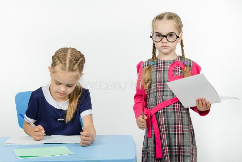 Строгий учитель стоя на студенте стоковое изображение