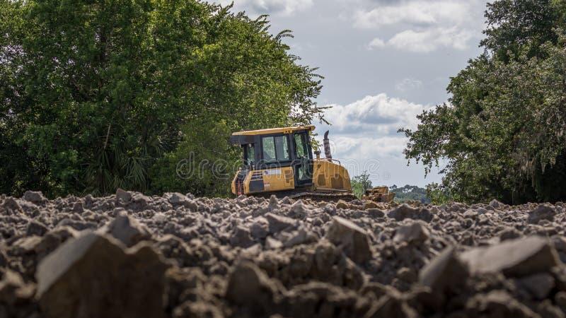 Строительная машина - передний затяжелитель Затяжелитель сидит в грязи на строительной площадке в древесинах стоковое фото