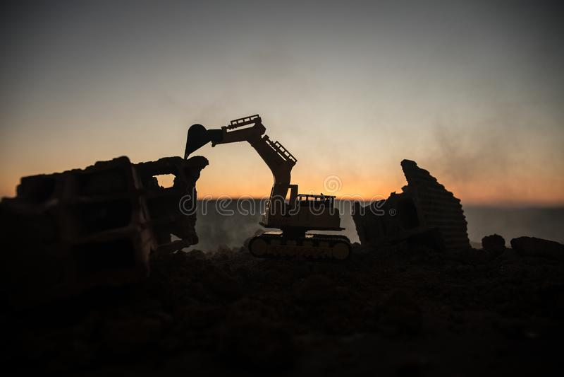 Строительная площадка на улице города Желтый экскаватор землекопа припарковал ночью на строительной площадке Промышленная концепц стоковые фотографии rf