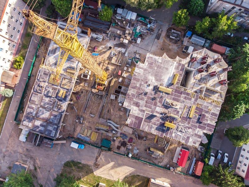 Строительная площадка при желтый кран башни снятый сверху стоковые изображения