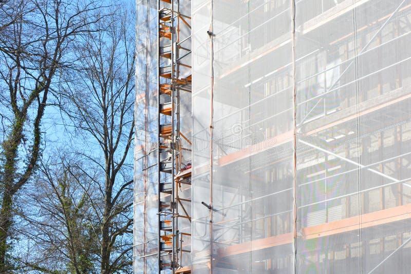 Строительная площадка с лесами на многоэтажном строя фасаде во время реновации стоковые фотографии rf