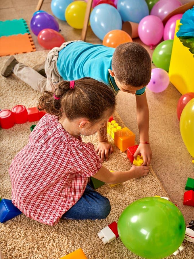 Строительные блоки детей в детском саде Дети группы играя пол игрушки стоковые изображения
