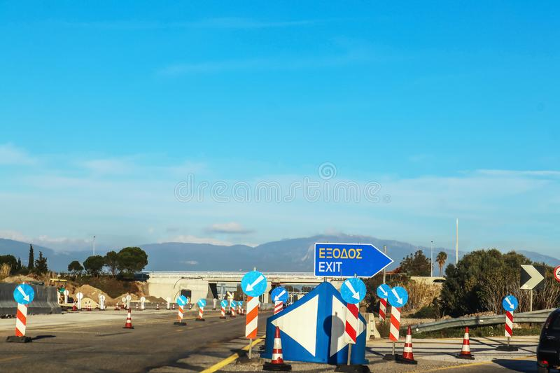 Строительство дорог в Греции с выходом подписывает в греческом и английском языке и сериях знаков направления дороги под мостом и стоковые изображения