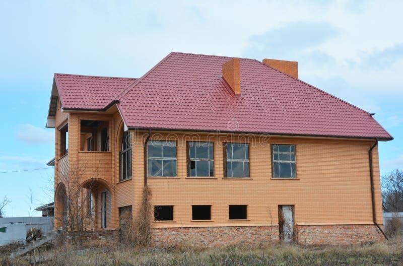 Строительство нового кирпичного дома со стальными листами крыши стоковые фотографии rf