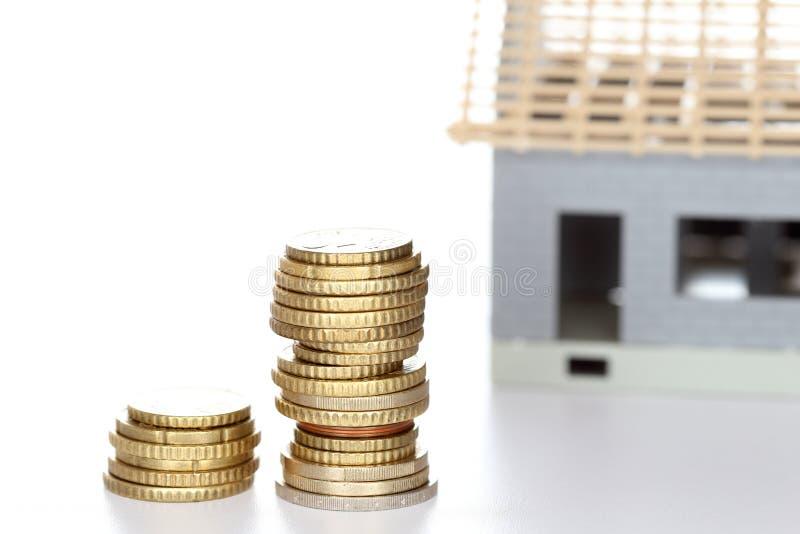 Строить дом с стогами денег стоковые фото