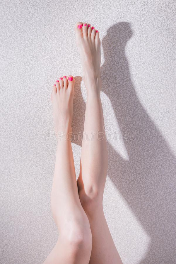 Стройные женские ножки с розовым лаком для ногтей. Slender female legs with pink nail polish on a background of a relief wall, hard light, concept beauty, underwear, barefoot, fit, caucasian, naked, nails, elegance, body, care, sexual, freshness, cream, wellness, fitness, lifestyle, figure, cosmetic, skin, woman, white, healthy, girl, spa, young, beautiful, slim, sexy, smooth, long, perfect, skincare, shape, attractive, pedicure, adult, person, clean, thin, soft stock image