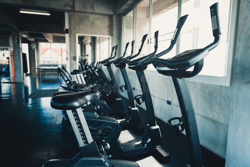 Строка велосипед оборудования тренировки в фитнес-клубе, интерьере центра подготовки спортзала и разработки задействуя машины, сп стоковое изображение rf