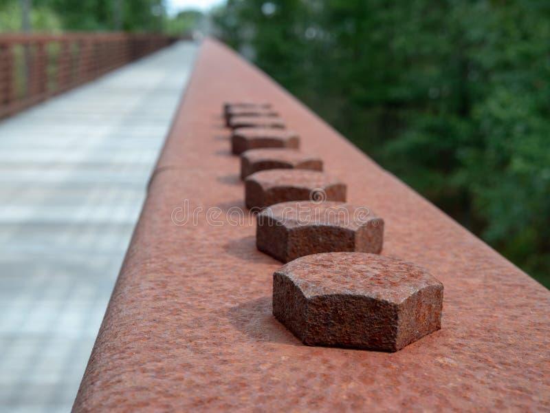 Строка винтов наговора в заржаветом стальном поручне на деревянном мосте на пути стоковая фотография rf