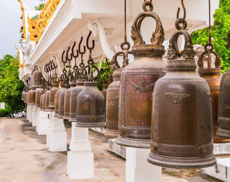 Строка выдержанных бронзовых колоколов в виске буддизма, Таиланде стоковое фото rf