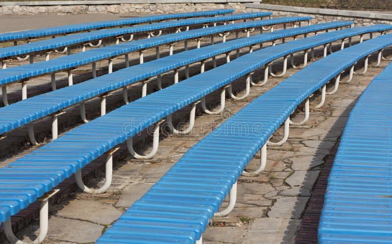 Строка голубых деревянных мест на фото трибуны зрителя Bench в парке стоковое изображение