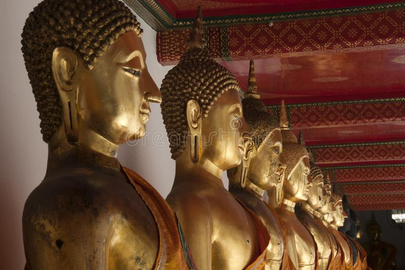Строка золотых статуй Будды в монастырях виска стоковая фотография