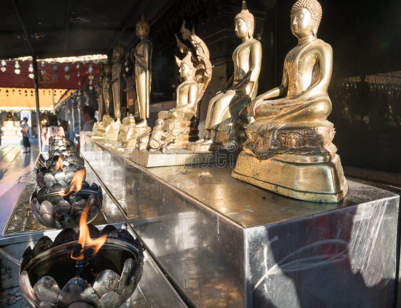 Строка золотых статуй Будды на стенде при пламена горя ниже стоковые фото