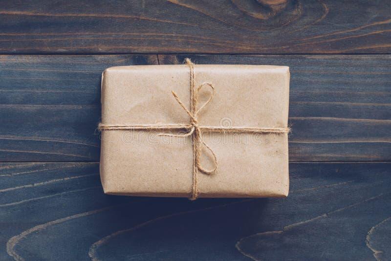 Строка или шпагат связанные в смычке на подарочной коробке бумаги kraft отсутствие деревянной стоковое изображение