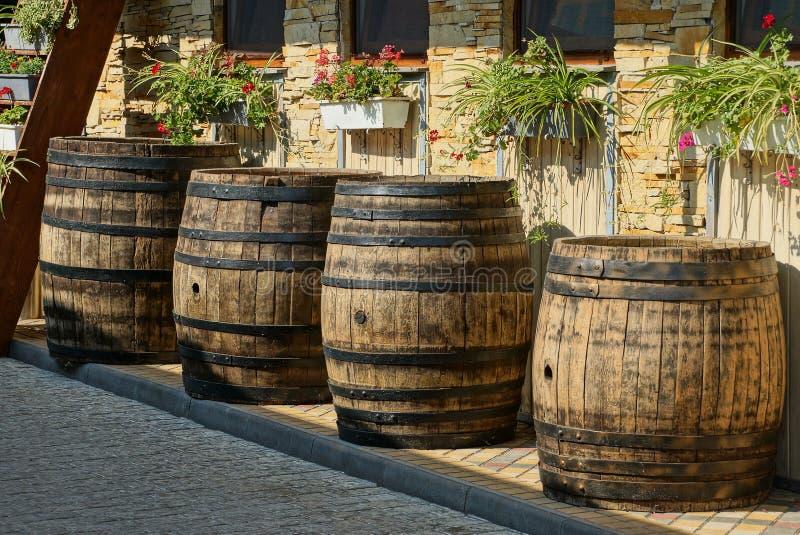 Строка коричневых деревянных бочонков стоит на тротуаре около стены с цветочными горшками и окнами стоковое фото